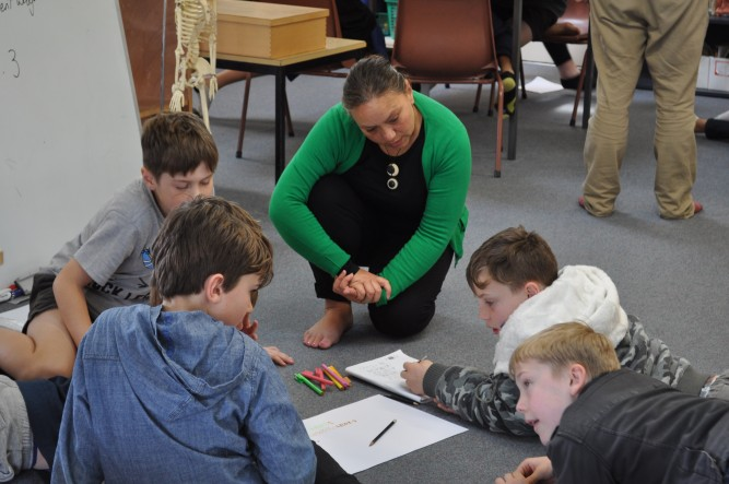 A teacher aide works with a group of students.
