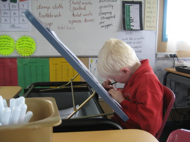 A student using a slope board for writing