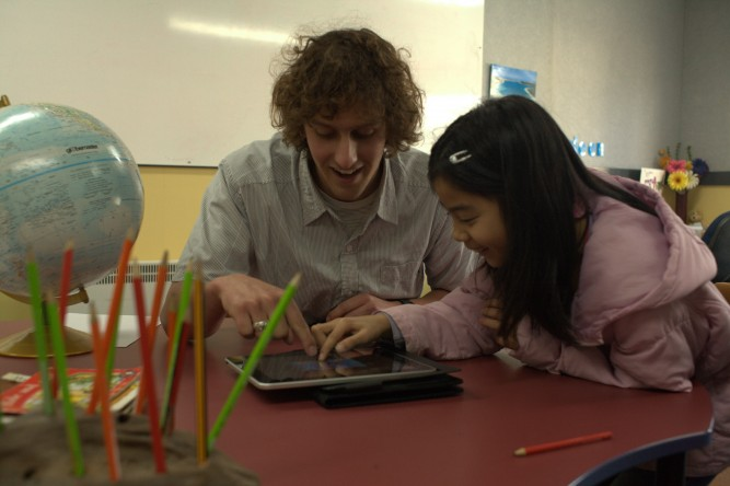 Student and teacher working on an iPad