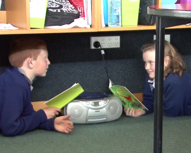 Students reading under bookshelves