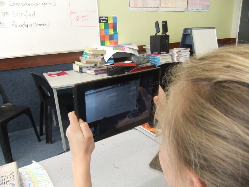 Student using iPad to read the whiteboard
